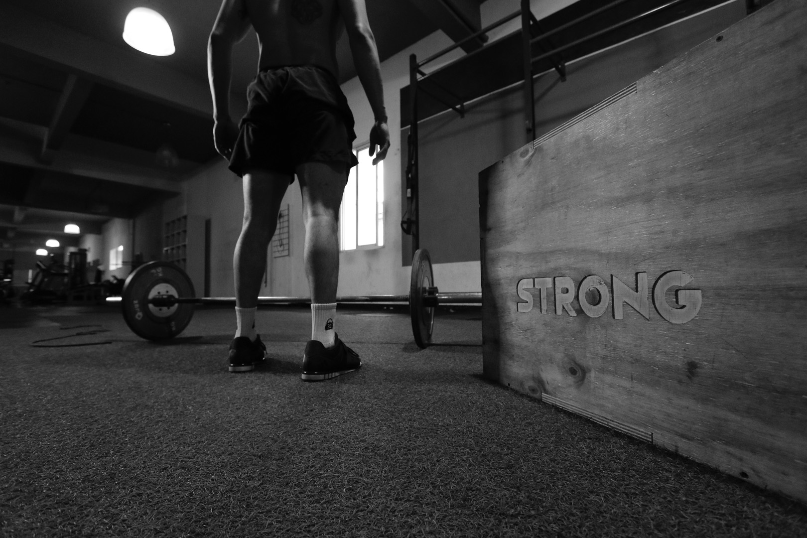 grayscale-photo-of-man-standing-beside-barbell-3112004